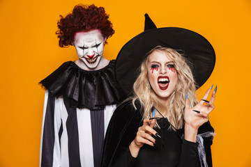 Image of witch woman and joker man wearing black costume and halloween makeup looking at camera, isolated over yellow background