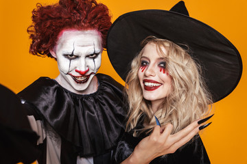 Photo of witch woman and clown man wearing black costume and halloween makeup taking selfie, isolated over yellow background