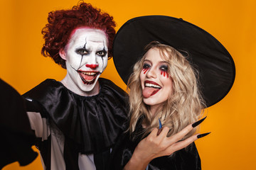 Photo of joyful witch woman and clown man wearing black costume and halloween makeup taking selfie, isolated over yellow background