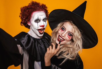 Photo of wizard woman and joker man wearing black costume and halloween makeup taking selfie, isolated over yellow background Fototapete
