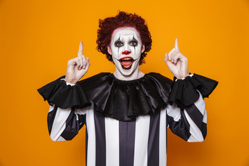 Happy clown man 20s wearing black costume and halloween makeup looking at camera, isolated over yellow background