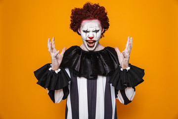 Ugly clown man 20s wearing black costume and halloween makeup looking at camera, isolated over yellow background