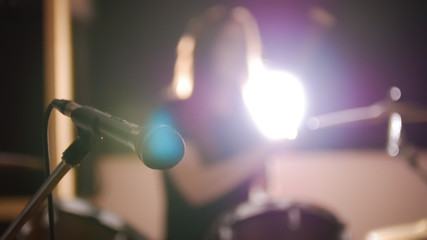 Red-haired girl practicing on a drum set in a dark room