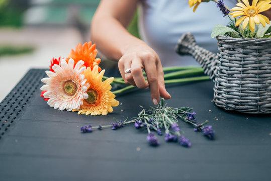 Arranging flower basket outdoors.