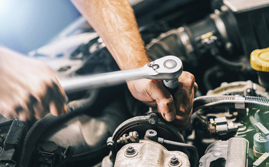Hands of car mechanic in auto repair service with wrench