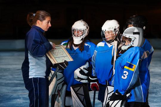Female coach explaining game plan to hockey team