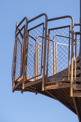 Metal spiral staircase before blue sky