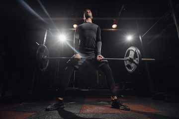 Training with barbell, dark background. Sporty man performs exercise of deadlift.