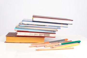 stack of colorful Books with School supplies lying on the table