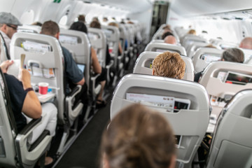 Interior of commercial airplane with passengers in their seats during flight.