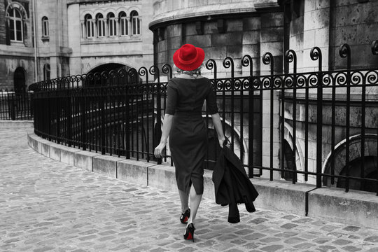 Young woman walking in Montmartre, Paris. Black and white photo with isolated red colour.