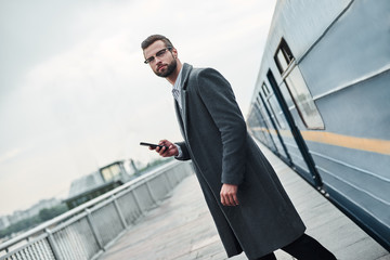 Business trip. Young businessman standing near railway holding smartphone looking aside pensive