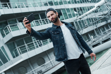 Outdoors leisure. Young stylish man standing on city street taking selfie photo on smartphone smiling happy