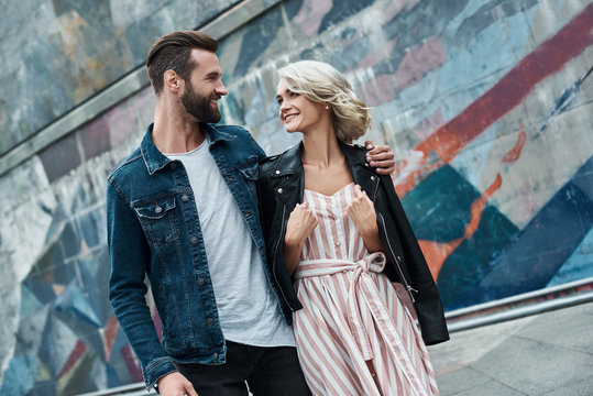 Romantic date outdoors. Young couple walking on the city street hugging looking at each other smiling cheerful