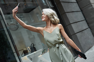 Fashion. Young stylish woman walking on the city street taking selfie photo on smartphone smiling cheerful