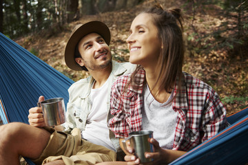 Couple relaxing in hammock in the forest