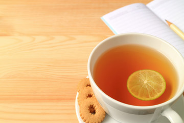 A Cup of Hot Lemon Tea with Cookies and Lined Note Papers on the Wooden Table, with Free Space for Text or Design