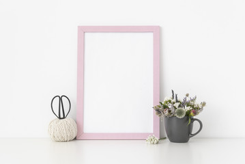 Pink a4 portrait frame mockup with dried field wild flowers in gray mug and vintage scissors on white wall background. Empty frame, poster mock up for presentation design. Template frame for text