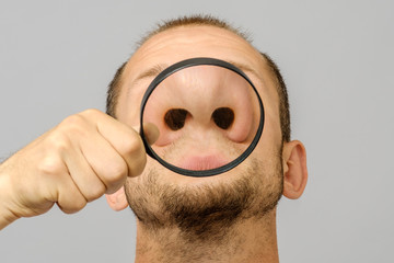 Fototapeta Portrait of caucasian man with magnifier makes fun face