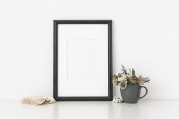 Black a4 portrait frame mockup with dried field wild flowers in vase and seashells on white wall background. Empty frame, poster mock up for presentation design.