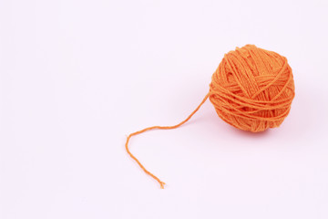 Orange ball of yarn on white background