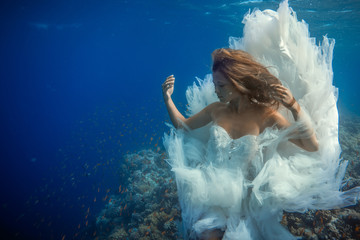 Girl underwater in blue sea against coral reef with red fish