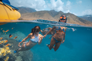 Three girls snorkeling and having fun in blue water