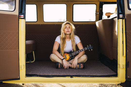 Young woman sitting in a van with a guitar