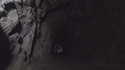 view deep cave with figures of two people with lanterns