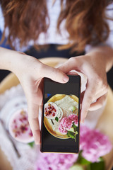 Close-up of woman taking cell phone picture of a drink