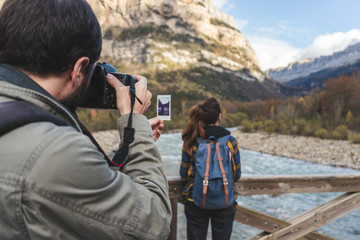 Spain, Ordesa y Monte Perdido National Park, man taking picture of woman and instant photo