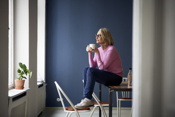 Mature woman at home with cup of coffee looking out of window