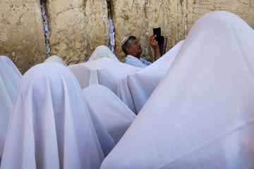 A Jewish worshipper holds up his mobile phone as others, covered in prayer shawls, take part in a priestly blessing during the Jewish holiday of Sukkot at the Western Wall in Jerusalem's Old City
