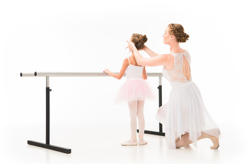 rear view of adult female teacher in tutu helping little ballerina exercising at ballet barre stand isolated on white background