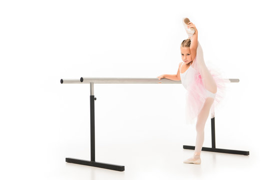 little ballerina in tutu stretching leg at ballet barre stand isolated on white background
