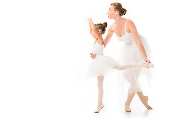 side view of adult female trainer in tutu helping little ballerina exercising isolated on white background