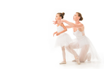 adult female trainer in tutu helping little ballerina exercising isolated on white background