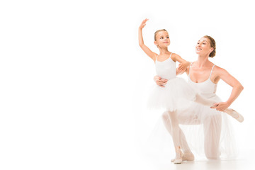 smiling adult female coach helping little ballerina exercising isolated on white background