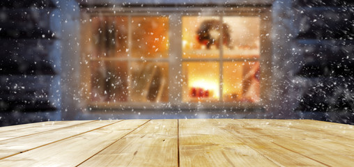 a festive wooden table by the window of a warm interior with free space for an advertising product