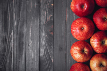 Dark wooden background with red apples on the right side of the frame