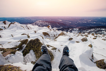 Legs in ski boot on background of snow and mountains
