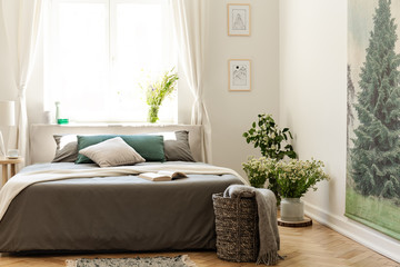 Nature bedroom interior in earth colors with a bed on a wooden floor, an evergreen tree poster on the wall and a bright window in the background. Real photo.