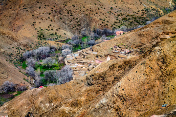 A small settlement in the Atlas Mountains. The mountain range is covered with bright green vegetation. Africa Morocco