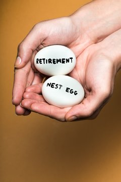 """Cupped Hands Holding Two Eggs With the Inscription """"Retirement"""