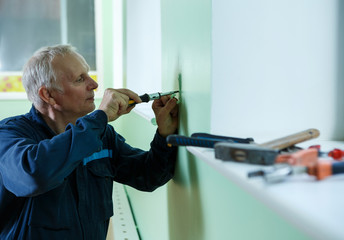 middle-aged senior man worker is working indoors fixing fitting screwing repairing