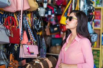 woman choosing and shopping handbag in store