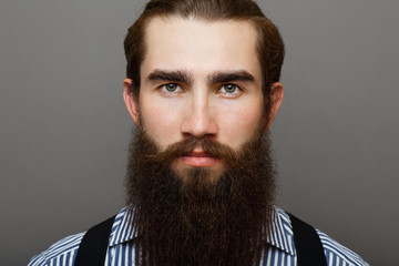 Handsome male portrait of a man with a beard.Man is dressed in a shirt and suspenders