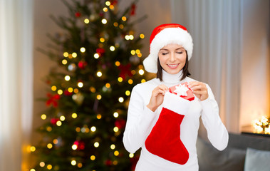 holidays and people concept - smiling woman in santa hat putting gift box into stocking over christmas tree lights background