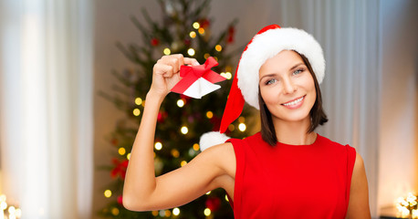 holidays and people concept - smiling woman in santa hat with jingle bells over christmas tree lights background