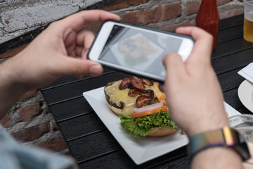 Man takes photo of food with mobile phone at an outdoor bar.  Taking a picture of your food with your phone. Hamburger, fries, and beer on a white plate outside on a black table focus on food.